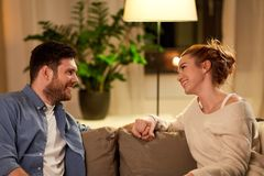 Happy couple talking at home in evening. Leisure and people concept - happy couple talking at home in evening royalty free stock photography
