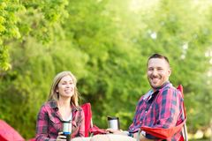 Couple talking and laughing on a camping trip. Royalty Free Stock Photography