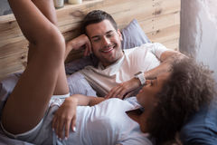 Happy couple talking in the morning. You are my sunshine. Happy young cheerful couple talking in the morning together while lying in bed and enjoying their Stock Photo