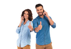 Happy couple talking on phones and make the ok sign. Happy casual couple talking on phones and make the ok thumbs up hand sign on white background Royalty Free Stock Image