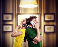Happy couple talking by phones. Happy men and women talking by mobile phones standing back to back Stock Image