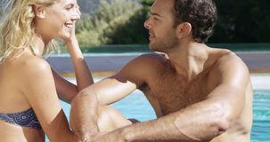 Happy couple talking. While sitting by the pool stock footage