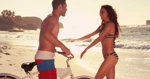 Happy couple talking at sunset. At the beach with bike stock video footage