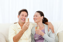Happy couple tasting champagne sitting on the sofa Stock Photo
