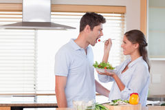 Happy couple tasting a salad Royalty Free Stock Image