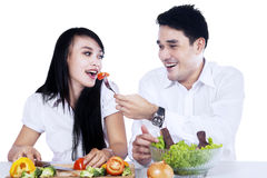 Happy couple tasting a salad Royalty Free Stock Photography