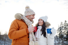 Happy couple with tea cups over winter landscape Royalty Free Stock Photos
