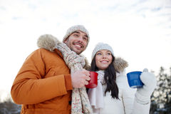 Happy couple with tea cups over winter landscape Stock Image