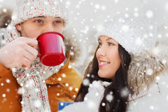Happy couple with tea cups over winter landscape Royalty Free Stock Photo