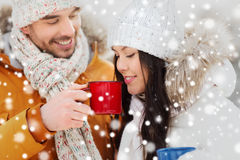 Happy couple with tea cups over winter landscape Stock Photography