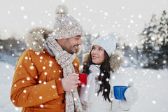 Happy couple with tea cups over winter landscape Royalty Free Stock Image