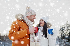 Happy couple with tea cups over winter landscape Royalty Free Stock Photography