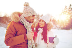 Happy couple with tea cups over winter landscape Stock Photo