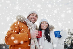 Happy couple with tea cups over winter landscape Stock Images