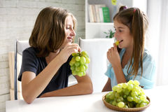 Happy couple of teenagers eating grapes stock photography