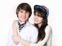 Happy couple teenagers having fun, smiling guy in bandana with g. Irl wears in cap with words New York isolated on studio white background Stock Photos