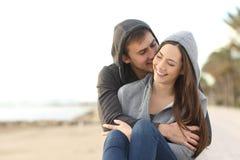 Happy couple of teens flirting on the beach. Front view portrait of a happy couple of teens flirting on the beach Stock Photos