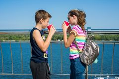 Happy couple of teens are walking, talking. Background city embankment, summer. Happy couple of teens are walking, talking. Background city embankment, summer royalty free stock image