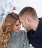 Happy couple tender embrace near Christmas tree stock photos