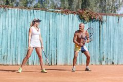 A pair of tennis players practicing outdoors. In full growth. The concept of sport. Happy couple of tennis players exercising outdoors. In full growth. The Royalty Free Stock Photos