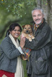 Happy couple with their dog. Portrait of a couple with their dog whilst out on a walk Royalty Free Stock Image