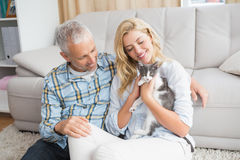 Happy couple with their kitten on the floor Royalty Free Stock Image