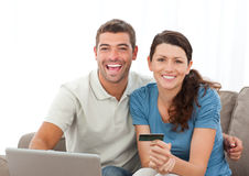 Happy couple with their laptop and credit card Stock Image