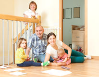 Happy couple with their offspring and grandmother on floor at ho. Happy couple with their offspring and grandmother sitting togetjer on floor at home in living Stock Images