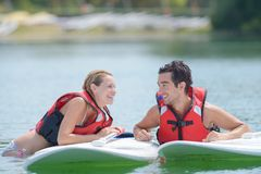 Happy couple and their paddle boards stock photos