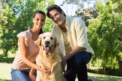 Happy couple with their pet dog in the park Stock Photography