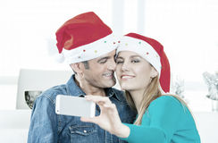 Happy couple in their 30s making a selfie for Christmas at home Royalty Free Stock Image