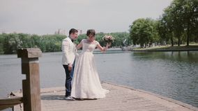 Happy couple on their wedding day dancing and having fun on a quay. River in a park in summertime. Wedding outfits stock video