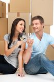 Happy couple toasting champagne flutes against cardboard boxes in new house. Stock Photo