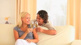 Happy couple toasting with Champagne. In their livingroom stock footage