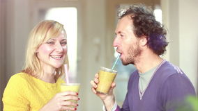 Happy couple toasting and drinking fruit smoothie stock video