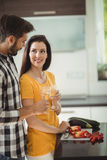 Happy couple toasting glasses of champagne while chopping vegetables in kitchen Royalty Free Stock Photography