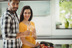 Happy couple toasting glasses of champagne while chopping vegetables in kitchen Stock Photos