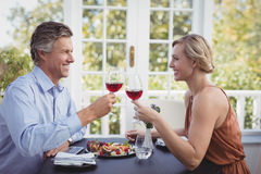 Happy couple toasting wine glass while having meal. In restaurant Royalty Free Stock Photo