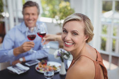 Happy couple toasting wine glass while having meal Stock Photos
