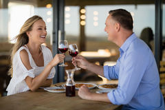 Happy couple toasting wine glass while having meal royalty free stock photos