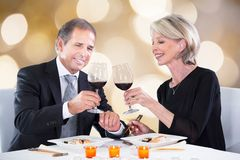 Happy couple toasting wineglasses in restaurant Royalty Free Stock Photos