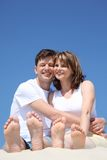Happy couple with toes up sitting on sand Royalty Free Stock Images