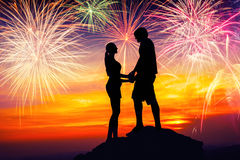 Happy couple together on rock and watching the fireworks Royalty Free Stock Images