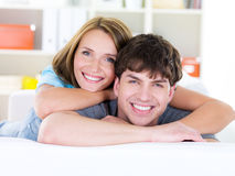 Happy couple with toothy smile. Happy portrait of beautiful young loving couple with cheerful toothy smile - indoors Royalty Free Stock Photo