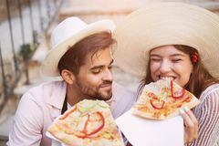 Happy couple of tourist eating pizza. On street Stock Image