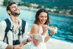 Couple of tourist eating pizza on street near the sea. Happy couple of tourist eating pizza on street near the sea Stock Photography