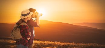 Happy couple tourist with photocamera at top of mountain at suns. Happy couple tourist with photo camera at top of mountain at sunset outdoors during a hike in Royalty Free Stock Photography