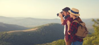Happy couple tourist with photocamera at top of mountain at suns. Happy couple tourist with photo camera at top of mountain at sunset outdoors during a hike in Stock Image