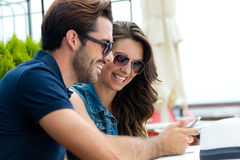 Happy couple of tourist in town using mobile phone. Stock Images