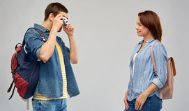 Happy couple of tourists with backpacks and camera. Travel, tourism and vacation concept - happy couple of tourists with backpacks and film camera photographing royalty free stock photo
